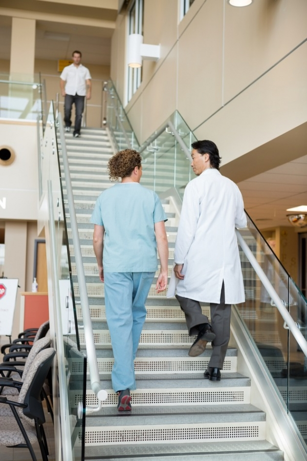 Doctor And Nurse Climbing Up Stairs In Hospital